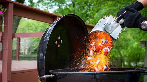 Gloved person dumping hot coals from chimney starter into a Weber Kettle grill - how to keep your charcoal grill hot