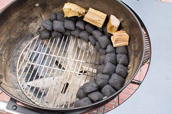 Crescent stacked charcoal briquettes with wood on top - Smoked Tri-Tip Beef - Grilling Inspiration