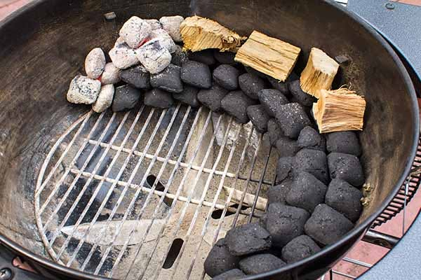 Crescent stacked charcoal briquettes with wood on top lit from one side - Smoked Tri-Tip Beef - Grilling Inspiration