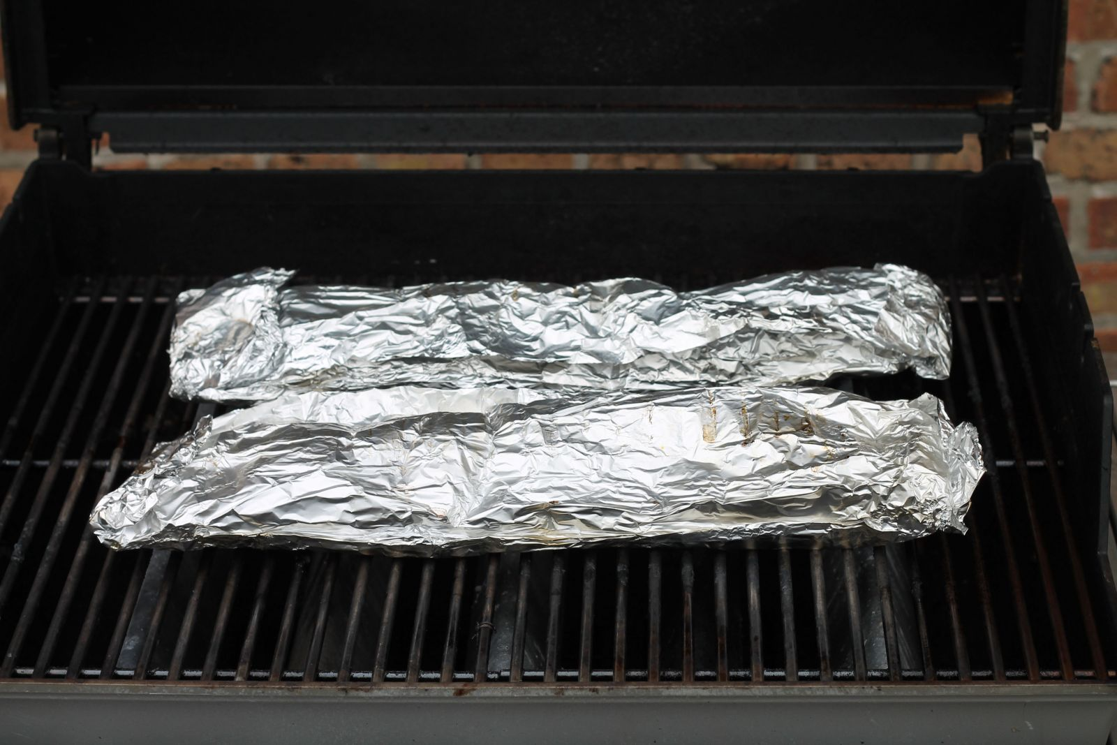 Packets of foil-wrapped ribs on the grill